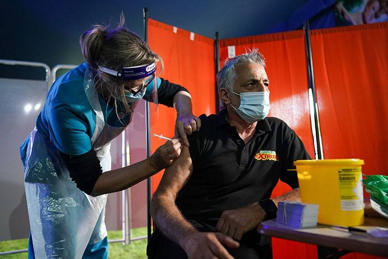 A doctor vaccinates a man in an outdoor clinic, at night.