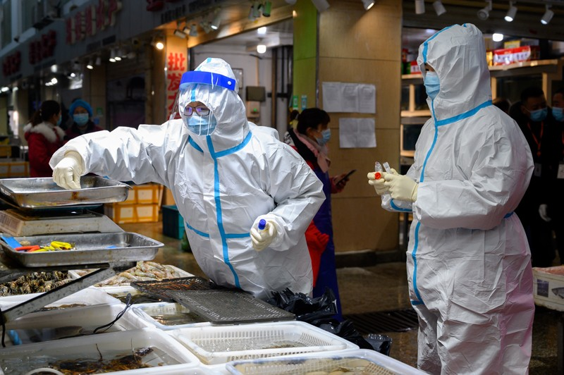 Health officers wearing personal protective equipment collect COVID-19 coronavirus test samples at a fresh market in China