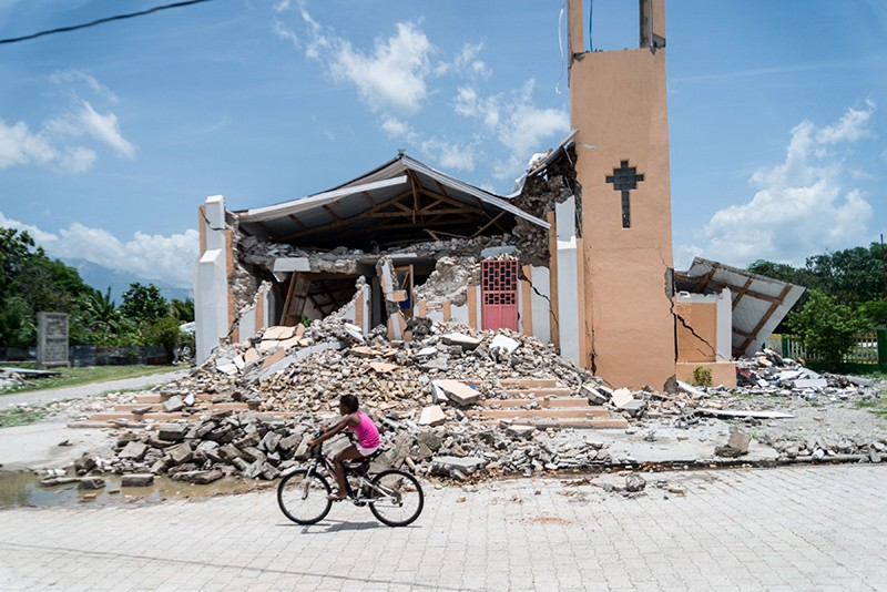 A child rides a bike on the road in front of a church that has been demolished by an earthquake in Chardonnieres, Haiti.