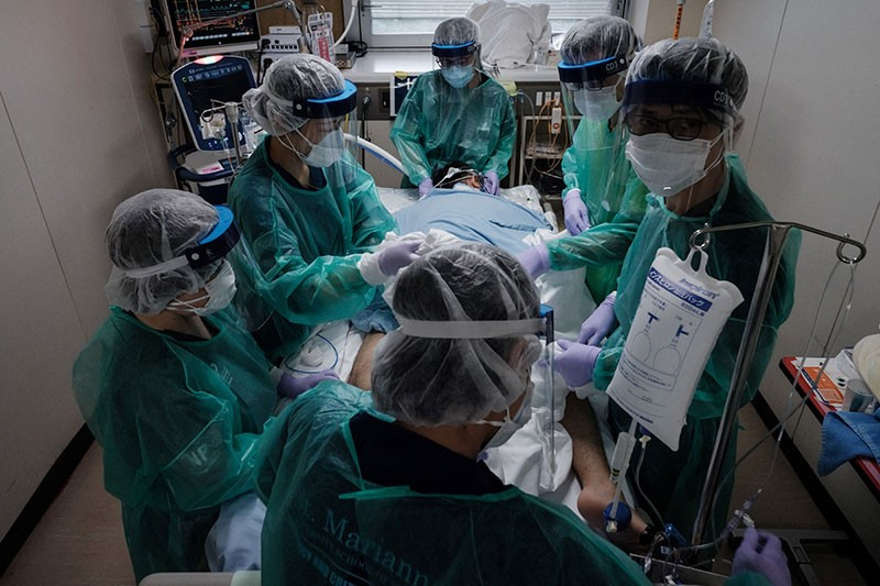 Medical workers in protective equipment take care of a COVID-19 patient on a ventilator at Yokohama City Seibu Hospital.