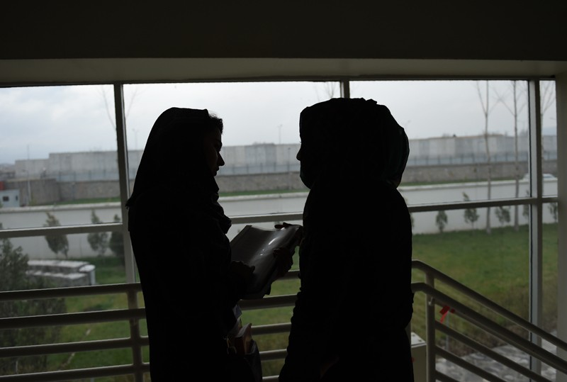 Two silhouetted Afghan students talk in the American University of Afghanistan