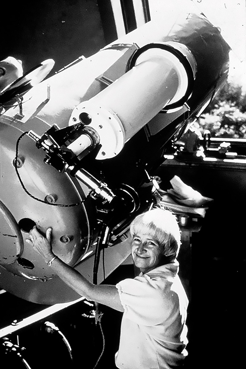 Black and white photo of Carolyn SHoemaker standing nest to a telescope in 1985