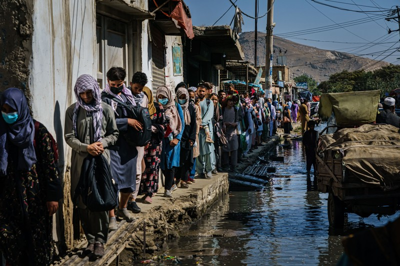 Afghans make their way through a flooded street towards a nearby airport entrance