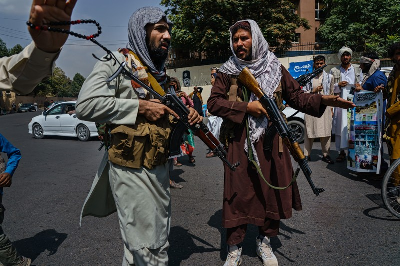 Taliban fighters controlling a rallying crowd