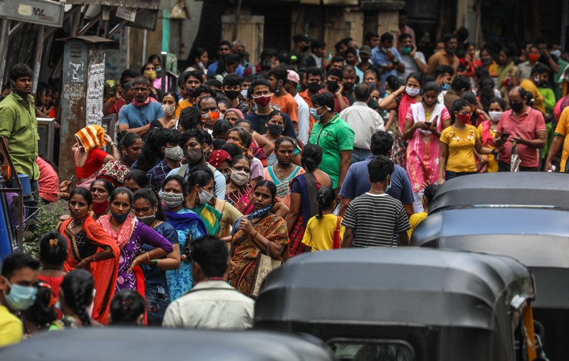 A crowd of people queue on a roadside to receive a covid-19 vaccine during a mass vaccination drive in Mumbai