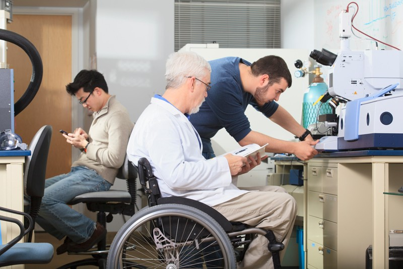 A professor in a wheelchair helps students in a lab