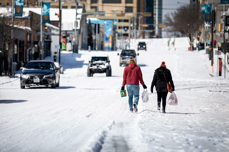 People carry groceries while walking down a snowy street