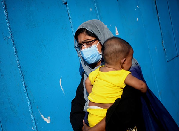 A woman wears a mask whilst carrying a child at a ferry terminal in Dhaka, Bangladesh.