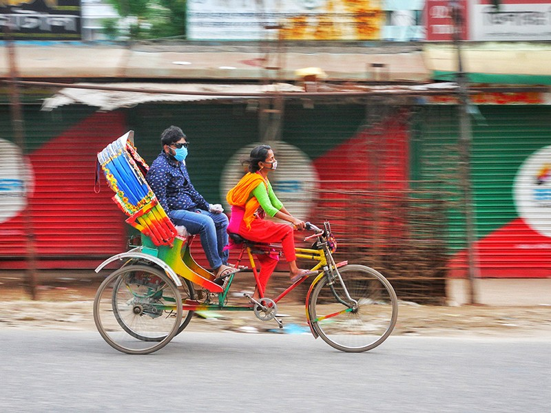 A woman wears a protective mask while driving a rickshaw with a masked passenger.