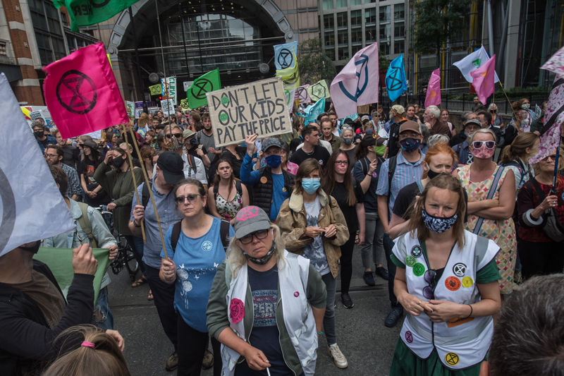 Extinction rebellion supporters march with drums, megaphones and banners through London's financial district