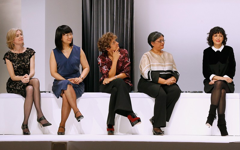 Five scientists sitting in a row on a white sofa.