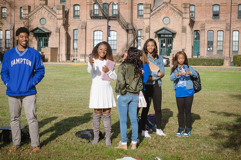 Five students stand on the lawn of a university.