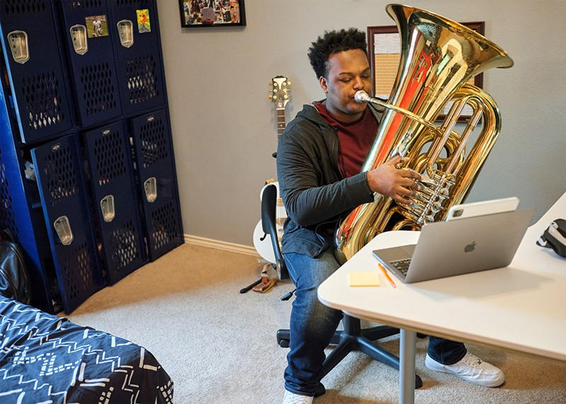 A person plays a brass instrument at Huston-Tillotson University as part of the African American Male Teacher Initiative.
