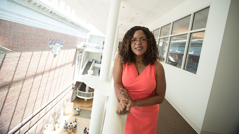 Ebony McGee leans on a railing at an open plan atrium building.