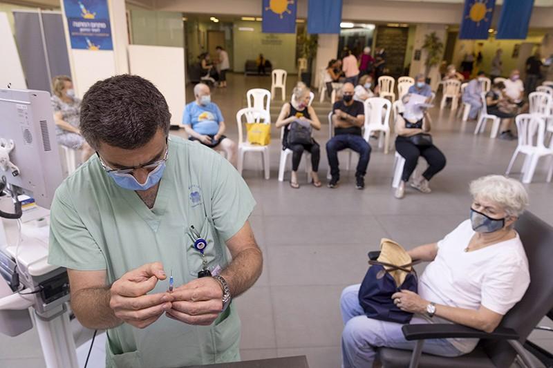 A health worker prepares a booster dose of the Pfizer-BioNTech Covid-19 vaccine in a waiting area in Tel Aviv, Israel.