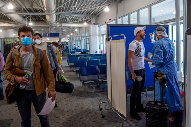 A member of medical staff performs a COVID test on a passenger in Athens airport
