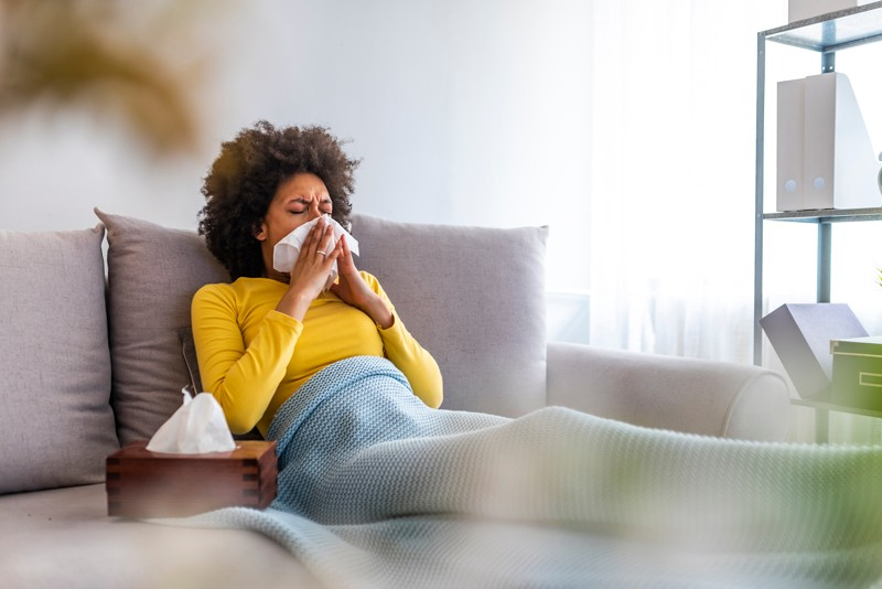 A young sick woman sneezing into a tissue at home
