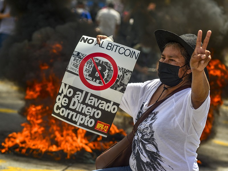 A protester holds a sign during a protest against President Nayib Bukele and bitcoin in El Salvador.