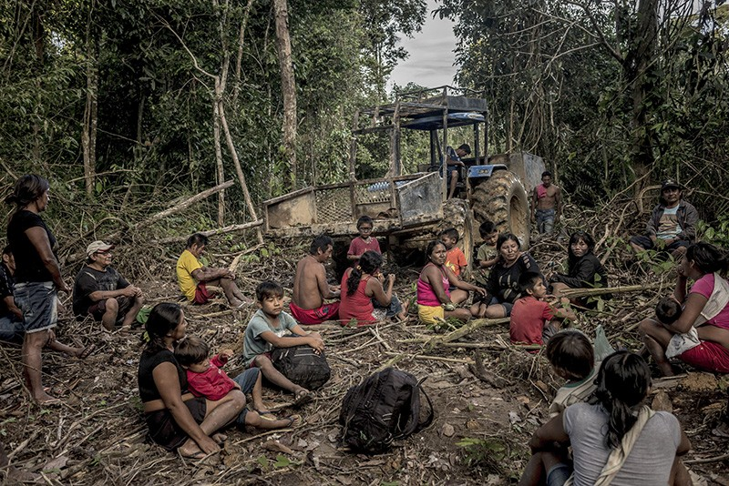 People take a break in front of equipment used to illegally mine their land in Brazil's Amazon.