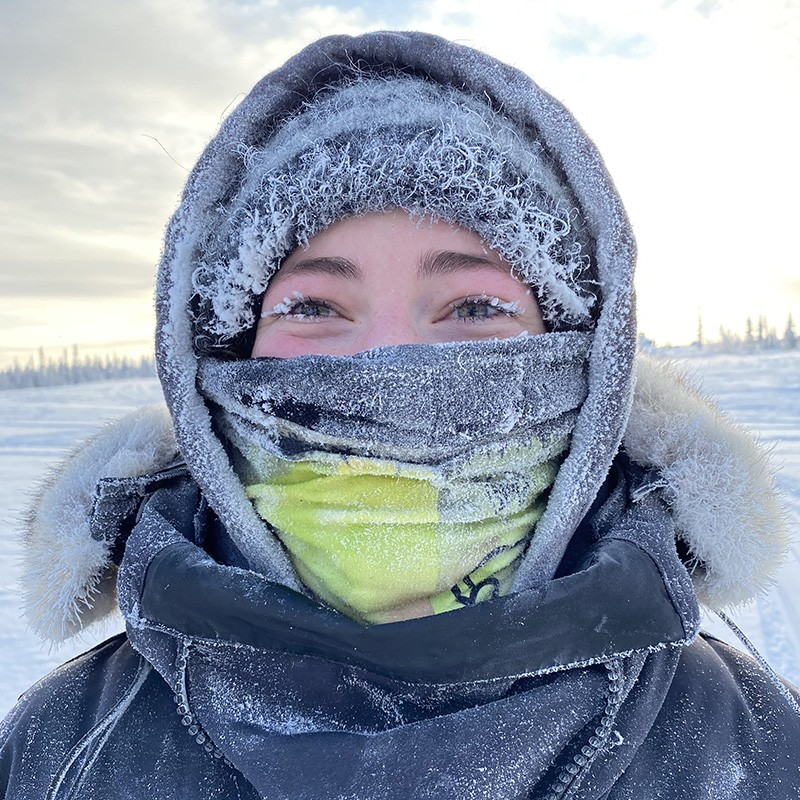 Erica Gillis in the subarctic ice area with ice and frost on her face and clothing.