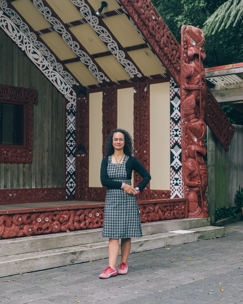 Ocean Mercier standing outside the wharenui of the University of Wellington, decorated with wood carvings and geometric panels
