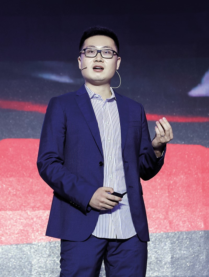 Xinge Yu stands on stage giving a talk