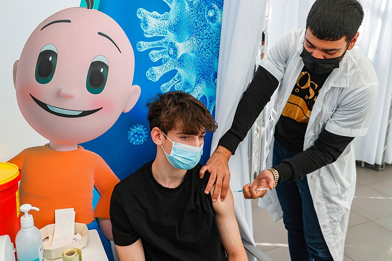 Jonathan, a 16-year-old teenager, receives a dose of the Pfizer-BioNTech COVID-19 vaccine in Tel Aviv.