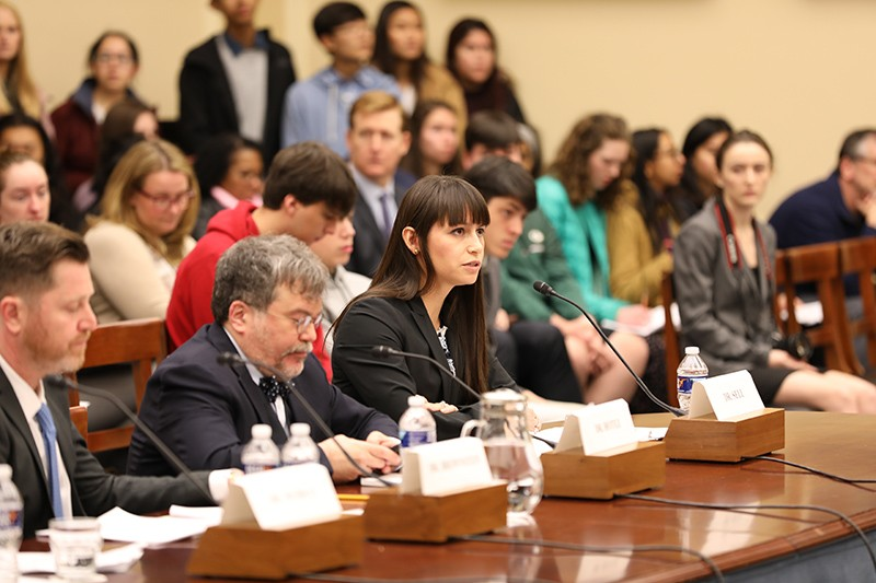 Tara Kirk Sell, surrounded by people and press, at her Congressional testimony.