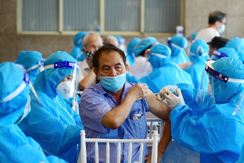 A man surrounded my medical workers in blue coveralls, face masks and visors, receives a covid-19 vaccine in Vietnam