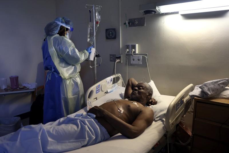 A nurse treats a patient with Remdesivir in hospital