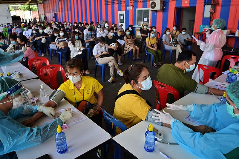 Medical staff check peoples vitals before administering doses of the CoronaVac or AstraZeneca COVID-19 vaccines in Bangkok.