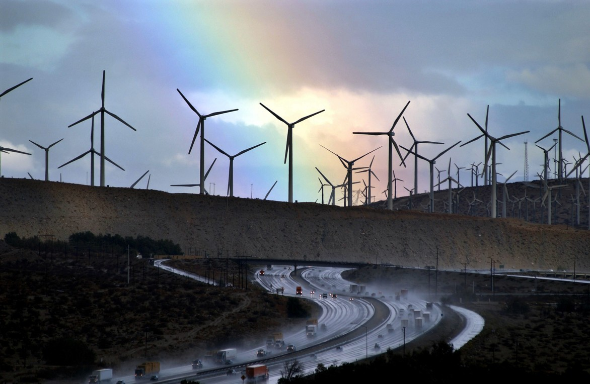 A rainbow forms behind wind-farm windmills near rain-soaked Interstate 10, Palm Springs, California