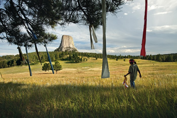 A boy places prayer flags in a tree near Devils Tower in Wyoming.