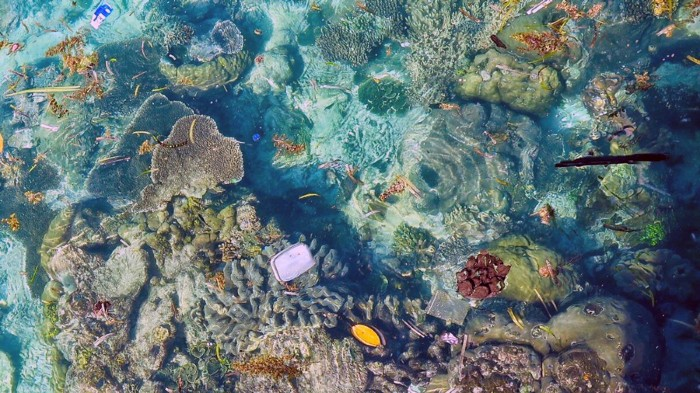 Aerial view of plastic floating over corals