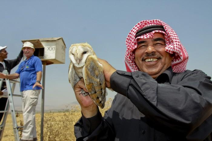 A Jordanian farmer holding Barn Owl in Kibbutz Sde Eliyahu, Israel