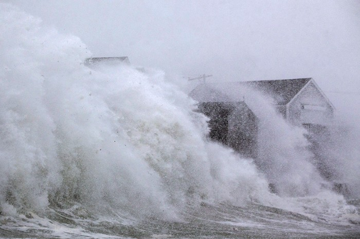 Large waves crash against houses near Boston