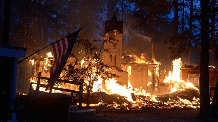 House engulfed in flames surrounded by a forest