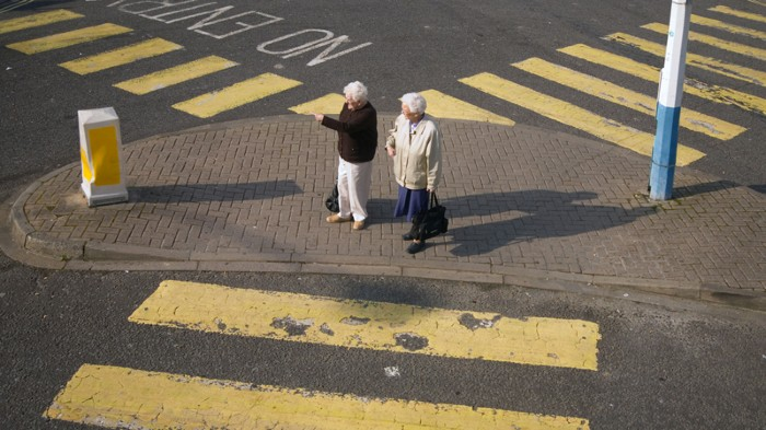 Two senior citizens crossing the road