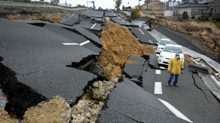 Man standing on a road damaged by an earthquake