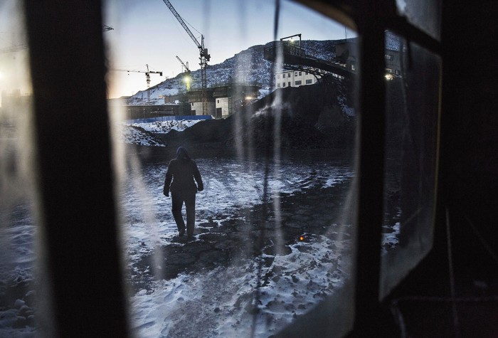 A Chinese coal mine worker walks in a sorting area at a coal mine on November 25, 2015 in Shanxi, China.