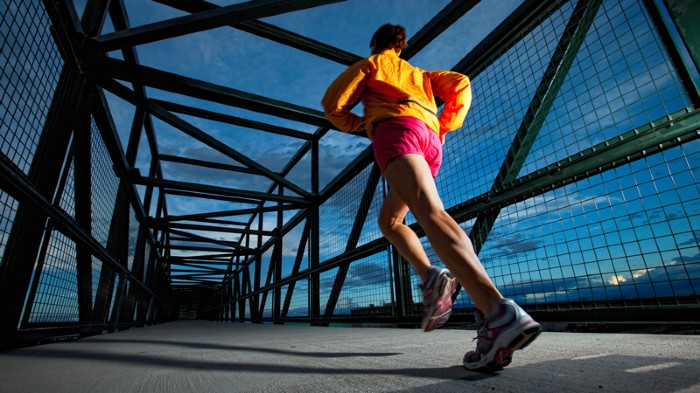A woman jogging on a bridge
