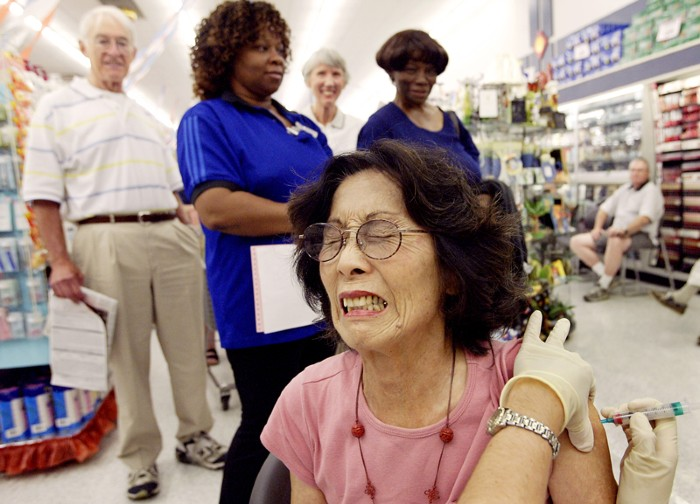 Woman reacting to getting a flu shot in a drug store