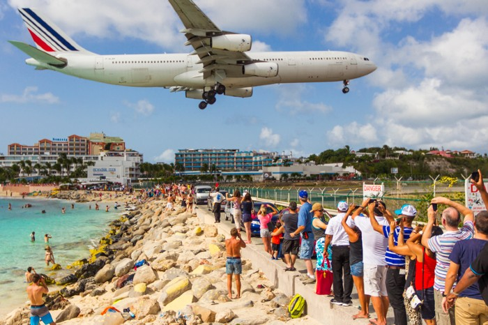 Tourists on the beach watch an aeroplane land