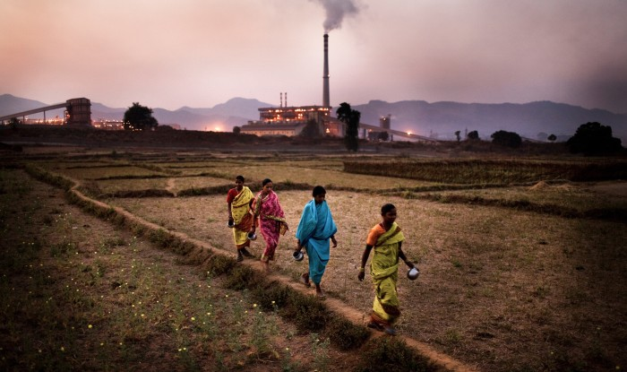Women walk through a field in front of the Vedanta Alumina plant in Lanjigarh.