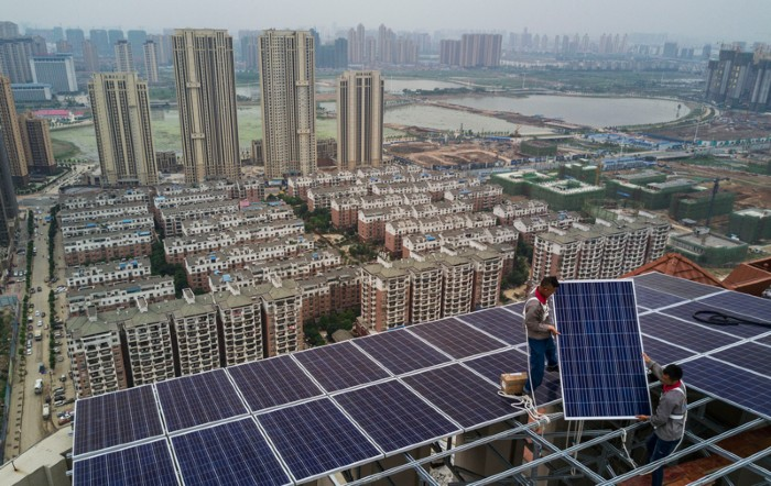 Workers install solar panels on a high-rise building in Wuhan, China.