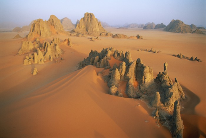 Pinnacles of sandstone rise through the orange dunes of the Karnasai Valley, a few kilometers from Chad's border with Libya.