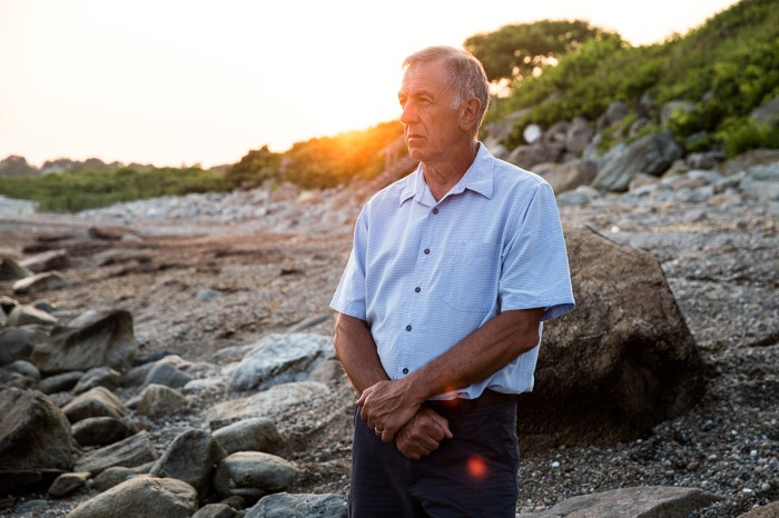 Dan Costas, now retired, gazes out towards the Rhode Island coastline at sunset.