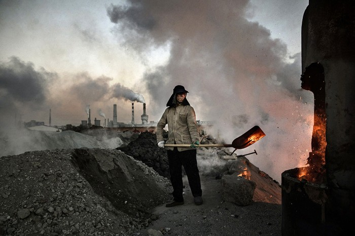 A worker shovels coal in a coal-fired factory in China