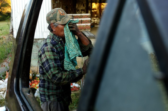 A farm worker wipes his face after an exhausting day in the fields.
