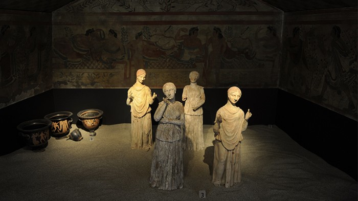 Reconstruction of the Etruscan Tomb of the Leopards. At centre are 4 lit statues of female mourners in different poses.